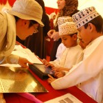 Omani schoolboys browsing excavation photos, 2011 (photo courtesy of Kristin Hopper).